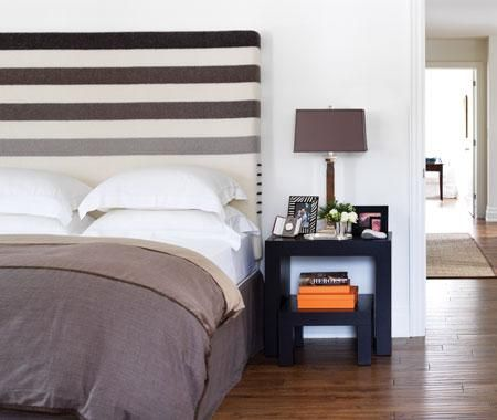 Hudson Bay blanket used as an upholstered headboard, stacked tables with orange Hermes boxes