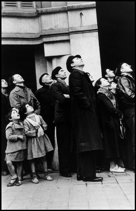 Barcelona, Spain. Watching an air raid over the city. Barcelona was being heavily bombed by fascist planes, as General Franco's troops rapidly approached. By Robert Capa, (January 1939)