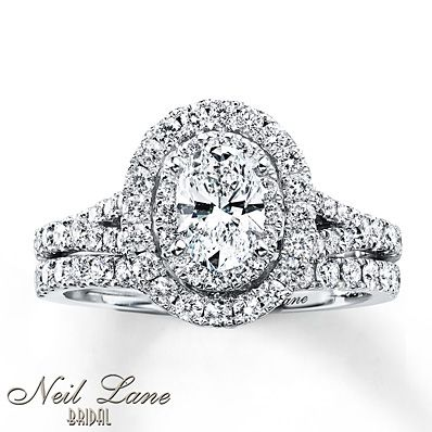 Two rows of round diamonds frame a captivating oval diamond ring of this stylish bridal set for her from the Neil Lane 174; collection. Additional round diamonds grace the band of the engagement ring. The 14K white gold bridal set has a total diamond weight of 1 1/2 carats. The Neil Lane signature appears on the inside of each band. Diamond Total Carat Weight 1.45 - 1.57 carats. Diamond Total Carat Weight 1.45 - 1.57 carats.