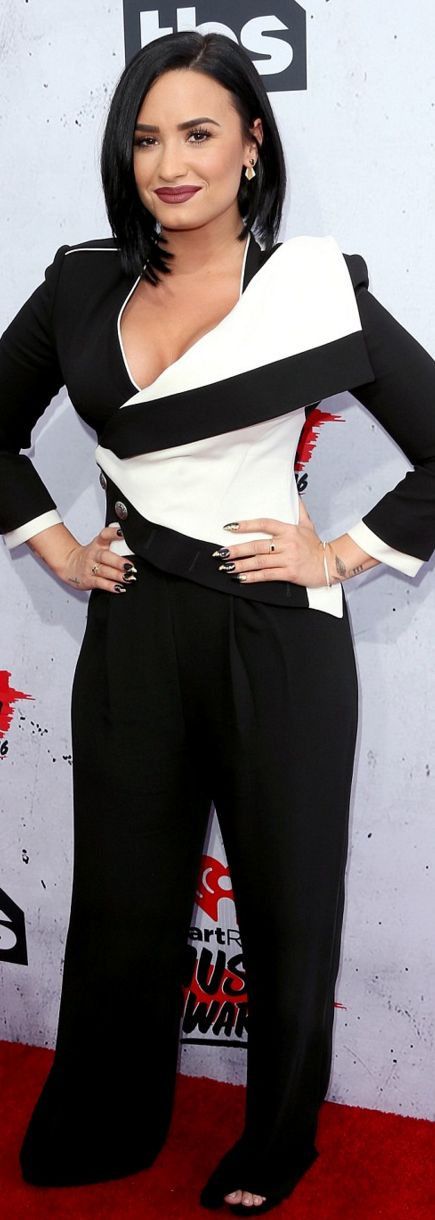 Who made Demi Lovato's black pants, white jacket, jewelry, and shoes?