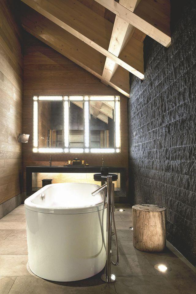 Se détachant sur un mur en granit noir, une baignoire blanche en îlot