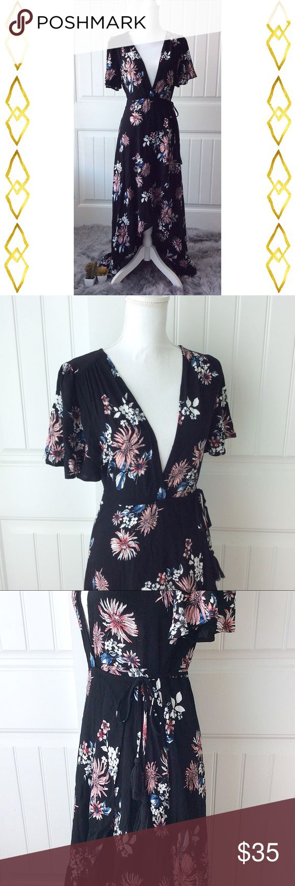 Floral Wrap Dress Soft and romantic floral wrap dress by Cotton Candy LA.  Dreamy florals play up the romance of this waist defining wrap dress set a flutter with a flowy hi-lo hemline.  Plunging v-neckline.  Gathered at shoulders. Short flutter sleeves.  Wrap front with self tie belt with tasseled ends.  Size is small but fits move like an extra small.  100% rayon. Cotton Candy LA Dresses High Low