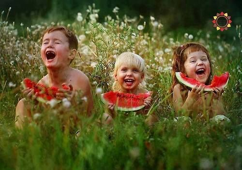3 laughing children in field holding slices of watermelon...