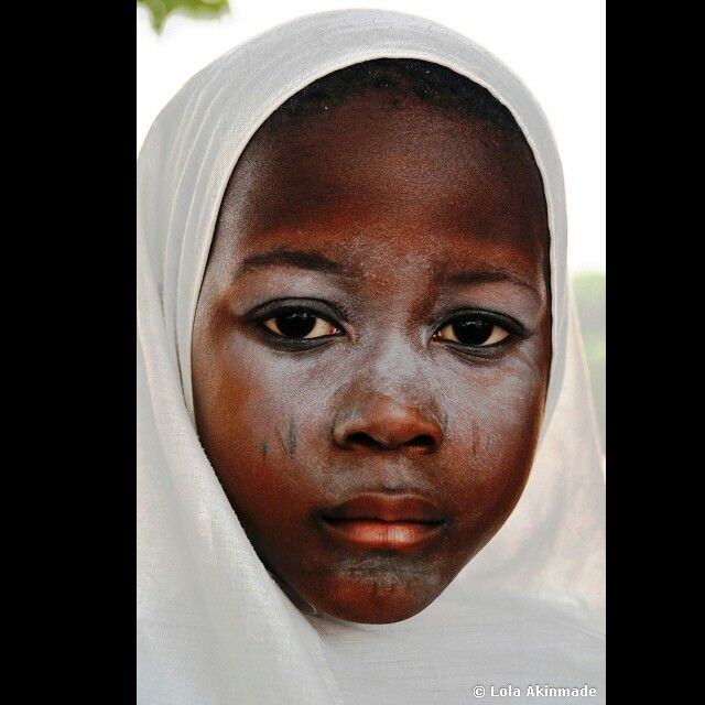 A young Muslim girl wearing a white hijab with white powder and Yòrubá tribal marks on her face | Lagos, Nigeria | Photo ©Lola Akinmade
