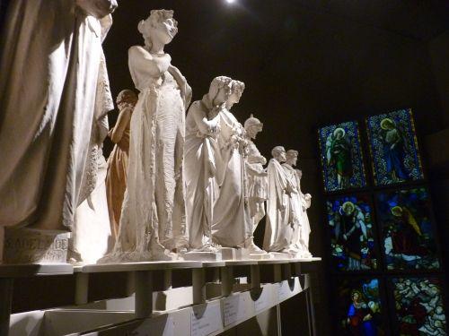 Sculture che ritraggono i santi. In primo piano, Sant'Adelaide. Sullo sfondo, uno scorcio di alcune vetrate. In mostra, vetrate ralizzate dall'inizio del '400 alla fine dell'800