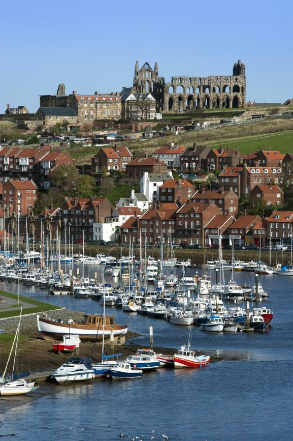 Whitby in North Yorkshire, England  Whitby is a little seaside town in the north of England.  In the background, the ruins of St. Hilda's Abbey on the East Cliff looms over the town.  Also on the East Cliff, is a churchyard which was the inspiration for Bram Stoker to write Dracula.  Captain Cook was also local and sailed from the port at Whitby for his famous trip circumnavigating the globe.  #ShareTravelExperience
