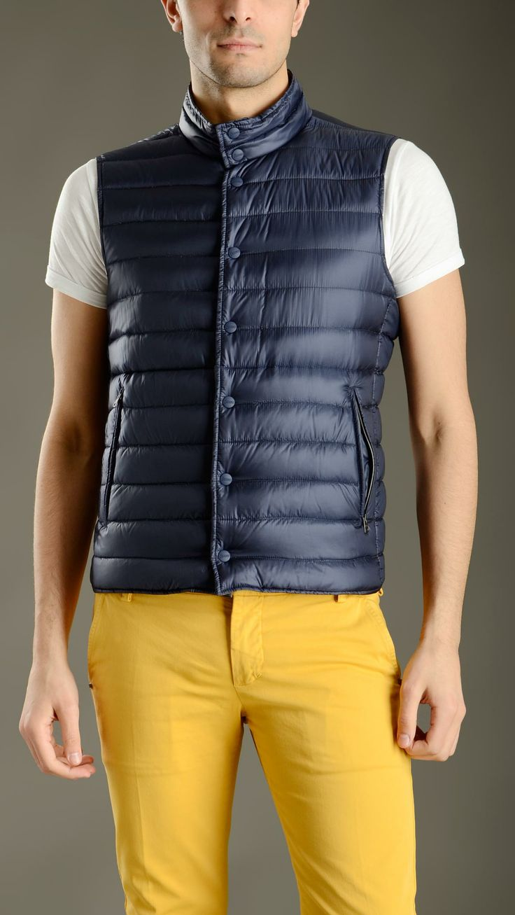 Blue waterproof ultralight quilted waistcoat featuring a stand up collar, horizontal stitch detailing, full lenght snap button fastening, two zippered side pockets, green reverse with two buttoned side pockets, 95% goose down, 5% feather down padding.
