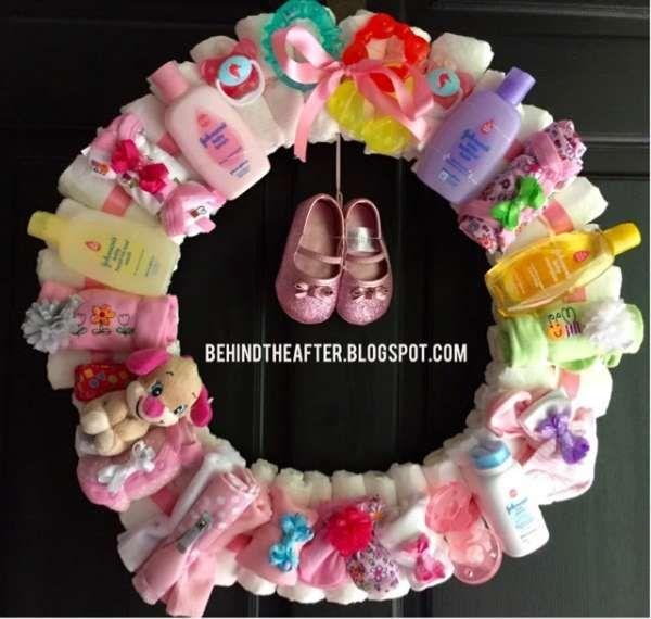 Une couronne de Noël avec des couches et des produits de spins pour bébé à offrir en cadeau. 25 magnifiques idées de gâteaux de couches DIY