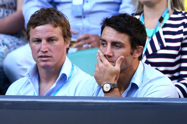 Melbourne Storm NRL players Brett Finch (L) and Cooper Cronk watch Bernard Tomic of Australia and Roger Federer of Switzerland in their third round match during day six of the 2013 Australian Open at Melbourne Park on January 19, 2013 in Melbourne, Australia.