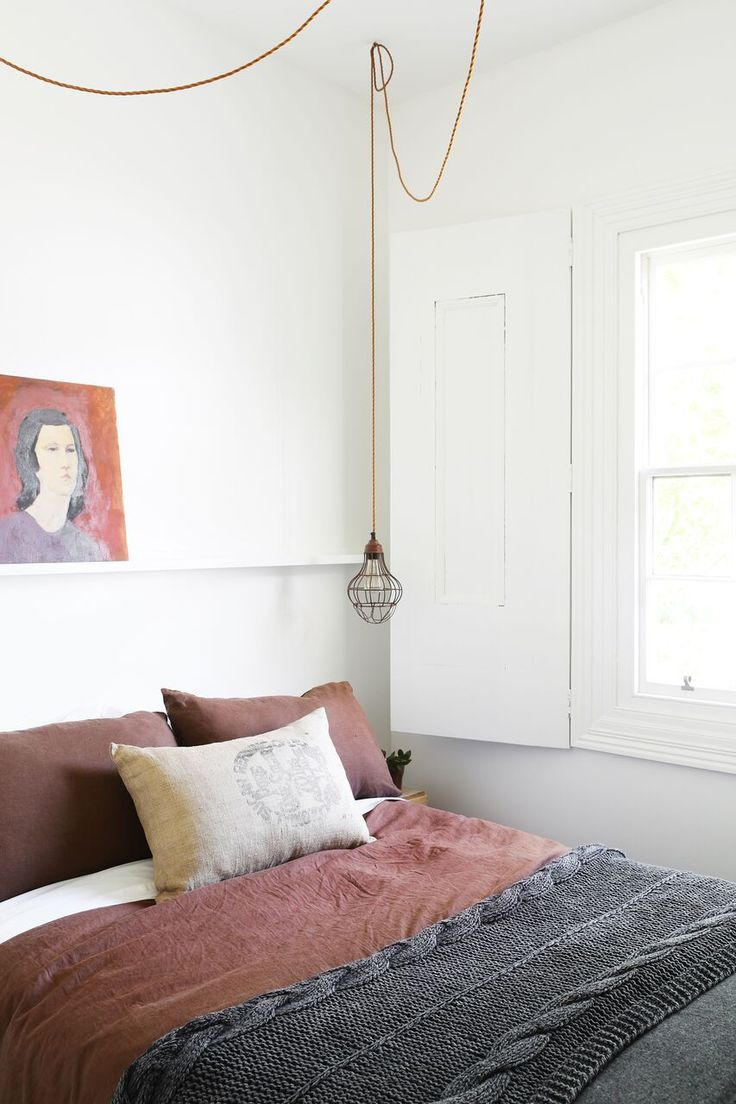 vintage painting propped on a narrow shelf over a Scandinavian interior bedroom