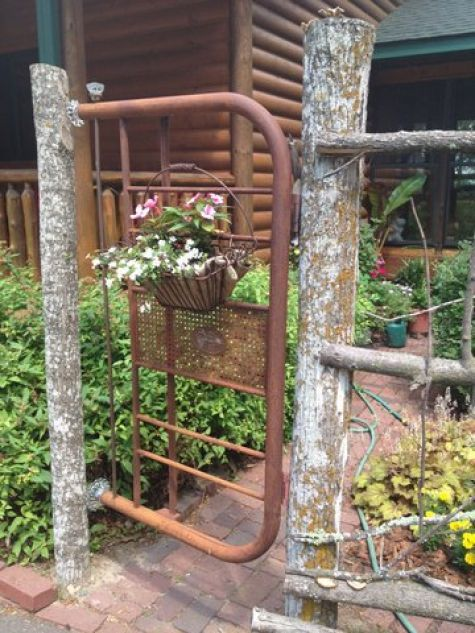Rusty garden gate made from old metal headboard