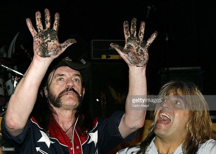 Motorhead lead singer Lemmy Kilmister (L) holds up his hands after he pressed them into concrete as Mikkey Dee laughs during their induction into Hollywood's RockWalk at the Whisky A Go-Go September 1, 2003 in Hollywood, California. The band will be performing tonight at the legendary club.    (Photo by Carlo Allegri/Getty Images)