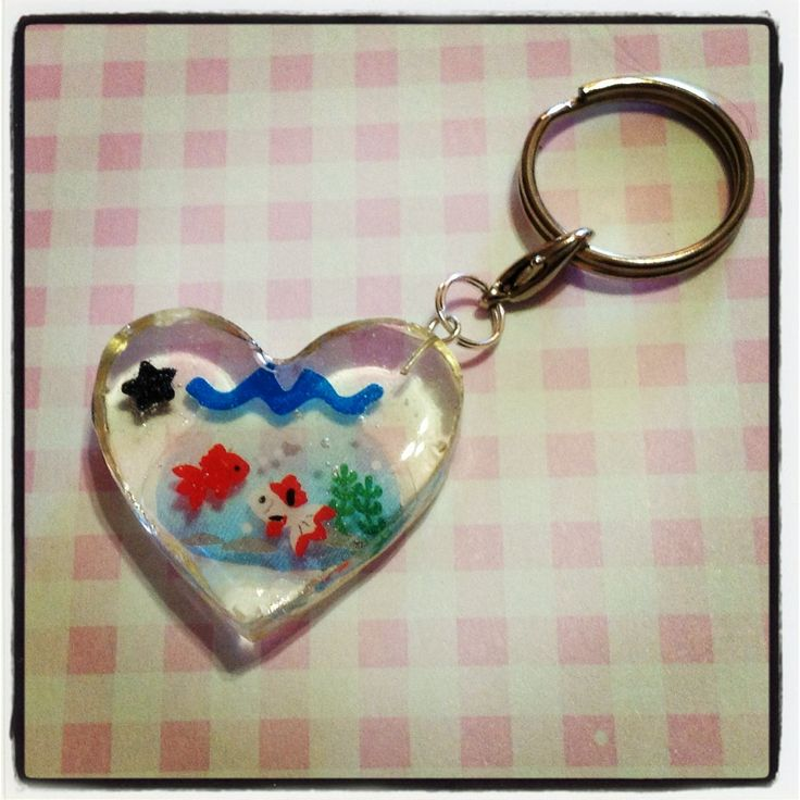 A red and white and red koi fish, or goldfish in a blue fishbowl, in a heart shaped resin keychain to hang all your keys from! A little black candy star sprinkle is also embedded in the resin, and this keychain is approx. 3cm wide and 3cm in length, and 0.5cm thick.  Given the preserving nature...