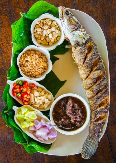 Thai dish called miang khum (เมี่่ยงคำ) is a DIY wrap of fresh raw slices of ginger, shallots, bird's-eye chilies, toasted coconut, peanuts, and a tamarind dipping sauce. This one is served with grilled snakehead fish | tielandtothailand.com