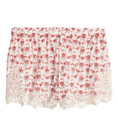 Naturhvit/Rød. En shorts i vevd kvalitet med trykt mønster og blondedetaljer nederst på bena. Snøring og elastikk i midjen.