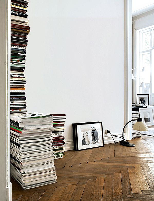 The stacks of magazines work well against the white wall and beautiful parquet floor. It's an effective way of adding texture while filling a space.