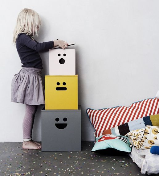 three plywood storage boxes with faces painted on them