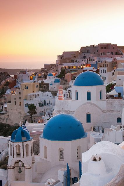 The characteristic blue-domed white houses of Oia on the island of Santorini in Greece at sunset. Sisterhood of the traveling pants was filmed on this Island! You can take a ferry (9 hours) here for about 50 euro from Athens! There are also flights and fa