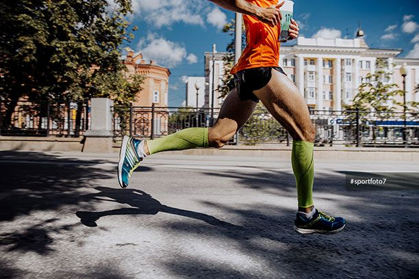 legs of a young male athlete in compression socks running marathon