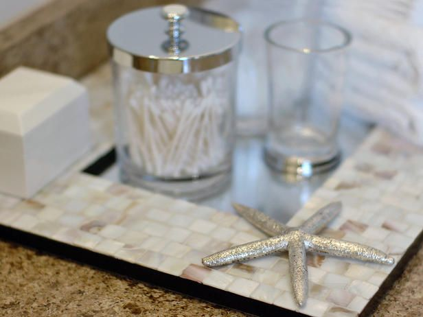 Bathroom essentials look neater piled atop a tray, but other household items, like painted cookie sheets or even mirrors, can do the job just as well. In the 2009 HGTV Green Home, designer Linda Woodrum used this mother-of-pearl mirror as a pretty base for glass jars and decorative accessories.