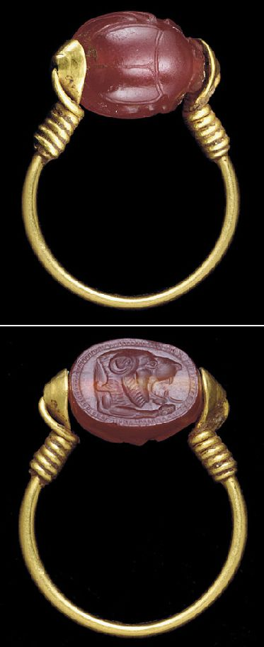 AN EAST GREEK GOLD AND CARNELIAN SCARAB FINGER RING   ARCHAIC PERIOD, CIRCA LATE 6TH CENTURY B.C.   The plain hoop oval in section with conical terminals, joined to the scarab by a plain wire threaded through the perforations of the stone and the terminals and coiled spirally along the hoop, the scarab carefully detailed, the underside engraved with the head of a roaring lion, his open mouth revealing fangs and a lolling tongue, a forepaw extending forward, enclosed within a hatched border