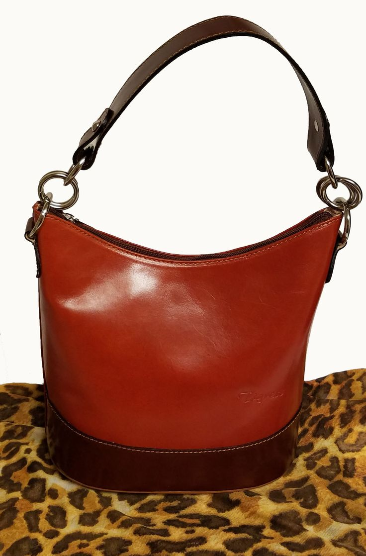 """This bag is made of rigid calf leather. Zip closure and single handle. External pocket with zipper. Detachable shoulder strap. Four protective studs on the bottom of the bag. Size: 9.5""""L x 10""""H x 6""""D"""