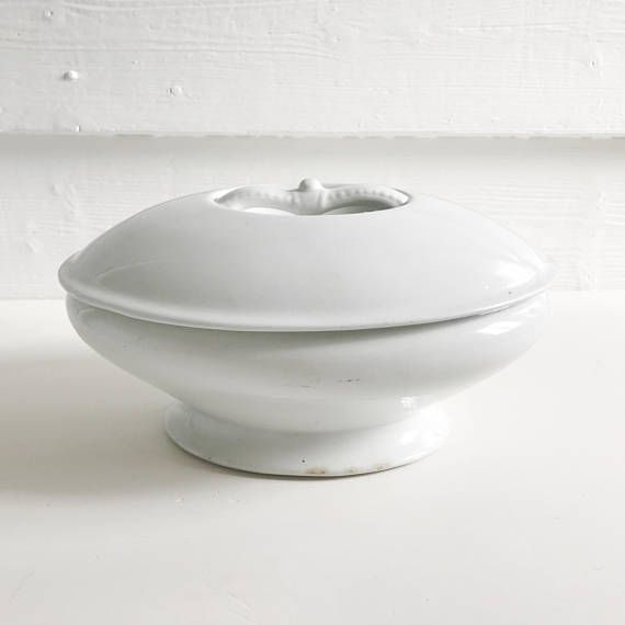 A white Ironstone oval-shaped tureen, with foot and recessed handle, made in England by J & G Meakin. This is a lovely, simple vegetable tureen in wonderful condition. It has the maker's stamp on the base and is free from any chips or cracks. There is a small amount of discolouration along the bottom edge of the foot as well as 4 small brown spots internally (please see pictures). Perfect or use and for display. 23cm long x 17.5cm wide x 13cm high. Due to the difficulty in accurately c...