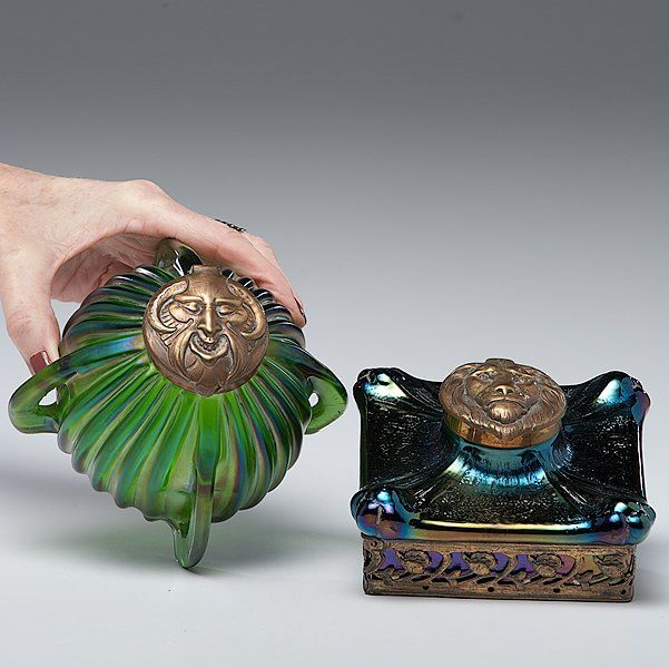 Loetz Inkwells    Austrian. Two art glass inkwells in the style of Loetz, including one spherical green inkwell, and one green iridescent square-shaped inkwell, both with brass lion's mask lids