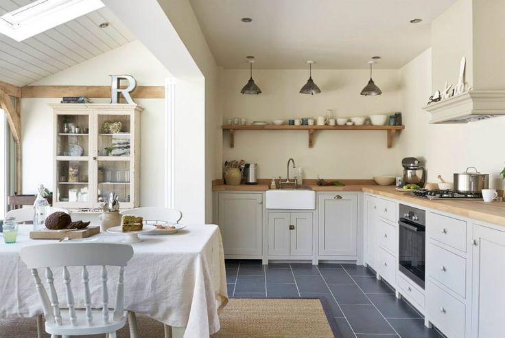 This is The Real Shaker Kitchen, by DeVOL.  The simple cottage kitchen design, painted in their Mushroom colour, works perfectly in this kitchen-diner extension. In the base cupboards there's a slimline dishwasher, under counter fridge, integrated oven and gas hob, along with plenty of storage drawers and cupboards.