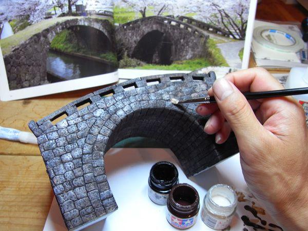 次はドライブラシ塗装にてディテールを浮かび上がらせます。  先ほどの色を白にちょっと加えて腰の強い平筆でササッと表面を履くように塗料を乗せて行きます。 石橋のディテールが浮かび上がってきますので楽しい作業です。