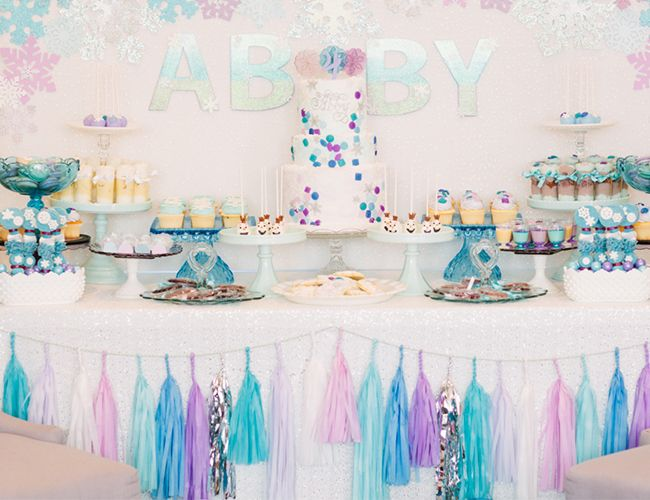 Frozen Birthday Party Dessert Table- Covered a 6ft x 4ft piece of cardboard with the prettiest tiny glitter snowflake fabric we found at Joann's, glued on a bunch of the cardstock snowflakes in a pattern and voila, backdrop done; Letters placed on the backdrop are chipboard letters found at Michaels that we painted and Modge Podged with white chunky glitter; Table was set with a gorgeous white sequin tablecloth from Candy Crush Shop; We strung a tissue paper tassel garland along the edge