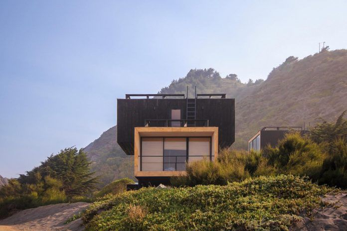Two wooden waterfront houses compressed by the sea and a cliff in Puertecillo by 2DM - CAANdesign | Architecture and home design blog