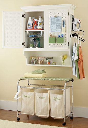 Lavanderia pequena e bem organizada. Os cestos separados para roupas claras e escuras são uma boa ideia