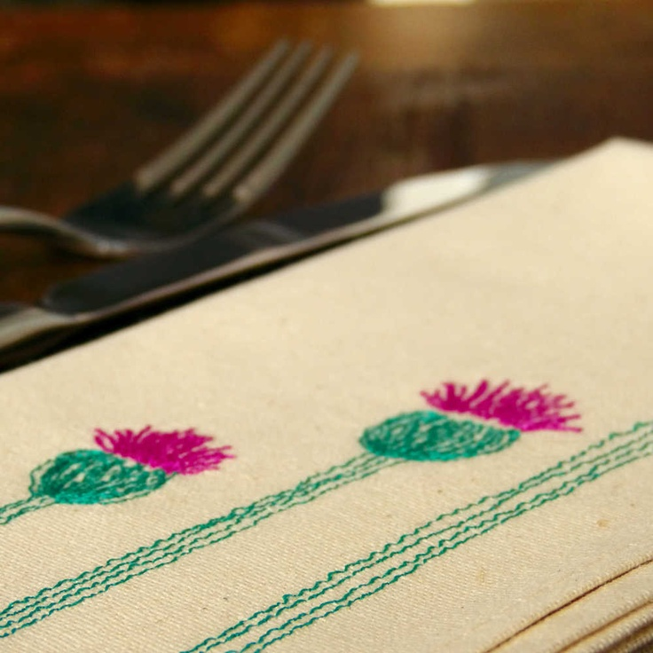 Triple Thistle Napkins. Set of 4 Napkins 100% Cotton. Natural or White Cotton, with Dusty Thistle Pink and Pine Needle Green coloured threads depicting three Scottish Thistles on each.We use free motion embroidery, in essence drawing with the sewing machine to apply our designs - no digitisation here...we freehand stitch the design using a standard (but rather smashing) sewing machine.