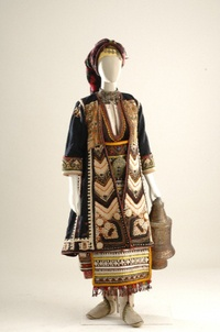 Bridal and festival costume from Makra Yefyra, a region that is now part of Turkey. After the population exchange of 1922-23, its inhabitants scattered throughout Western Macedonia and Thrace. The costume consists of a cotton chemise and sleeveless one-piece dress embroidered with special motifs. Both the long-sleeved overcoat and the apron have all-over embroidery. The waist is belted with a red sash over which is the bakirozounaro, a belt signifying betrothal. On the feet are white boots…