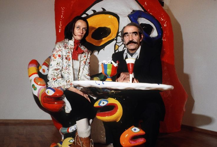 Niki de Saint Phalle and Jean Tinguely and sitting at a table, which has been designed and realised by Niki de Saint Phalle, pictured in the retrospective exhibition in the gallery  Bischofberger in Zurich, 1980