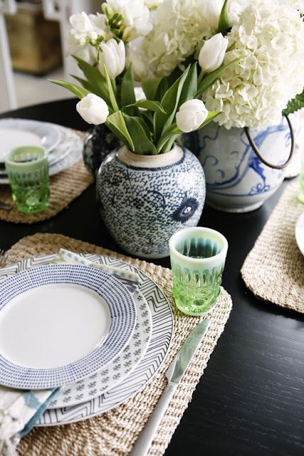Woven placemats, blue/navy plates, vases, tulips, and hydrangeas make for a lovely table setting.