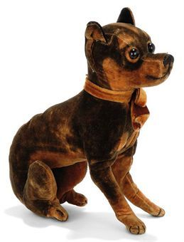 A SEATED VELVET CHIHUAHUA, brown and black, replaced boot button eyes and black stitching, <I>circa 1910 --7in. (18cm.) high</I>