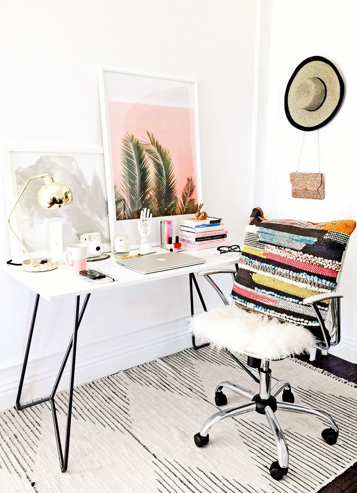 Workspace with white walls, white desk, beige patterned rug, silver chair with colorful pillow, gold lamp, and colorful books and artwork
