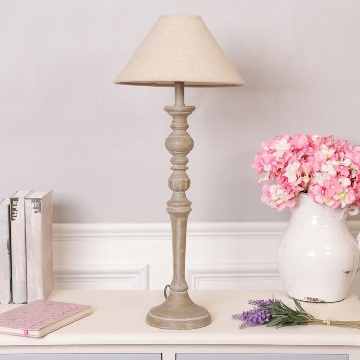This table lamp featuring a country style design is ideal for creating a warming ambience to any room in your home made from wood finished in a light