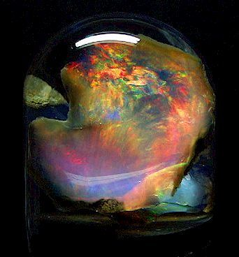 Fire Opal from Virgin Valley, Nevada!  ...colors change when the Opal is viewed at different angles.  The 4.5 cm by 4 cm Opal is displayed in a water filled specimen glass.