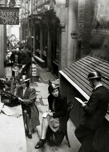 c1940: Girl clerks from a London office, working outside in steel helmets, after being forced outside by bomb damage to their building (Photo by Rolls Press/Popperfoto/Getty Images)