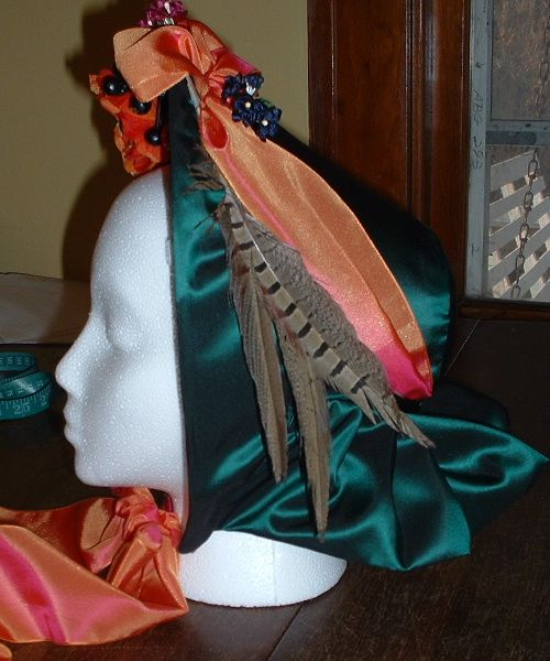 """The spoon bonnets pictured here are made to sit on top of a low chignon (bun). They have wide ribbon ties and """"anchor ties"""" that are sewn behind the ribbon ties. Anchor ties are narrow ribbons that are tied before you tie the wide fancy ribbons so that most of the stress of the bonnet would be put on the anchor ties. This allowed the wider ribbons to be tied nicely rather than having to tie them in a tight and unbecoming bow. Sometimes if the ribbons were especially stunning and the lady…"""