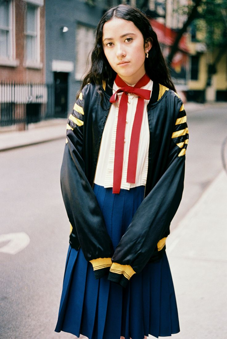 Manon Macasaet, 16, in a vintage bomber jacket and a Gucci dress with a pleated skirt and red ribbon