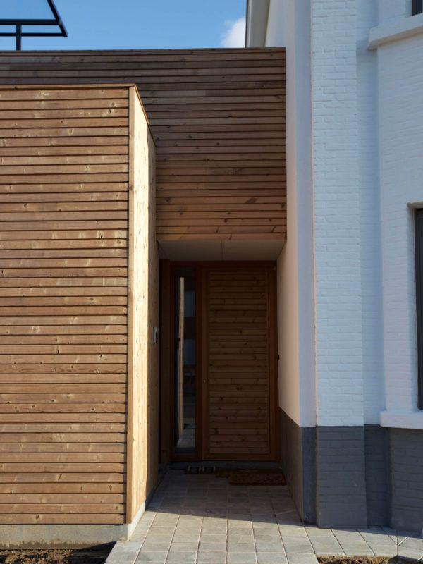 Het witte woonerf, nieuwe inkomhal met houten gevelbekleding – Ypsilon Architecten