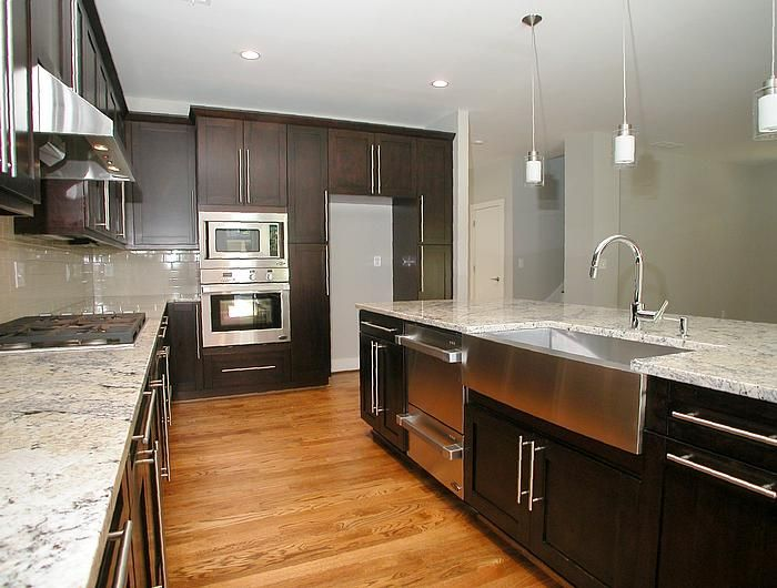 A modern style kitchen in a new home in Decatur, GA. The kitchen features espresso wood cabinetry, granite countertops, subway tile backsplash, stainless steel farm sink, built-in pantry, pendant lighting and an oversized island that overlooks the family room. The DCS kitchen package includes gas cooktop, built-in oven and microwave and a double drawer dishwasher.