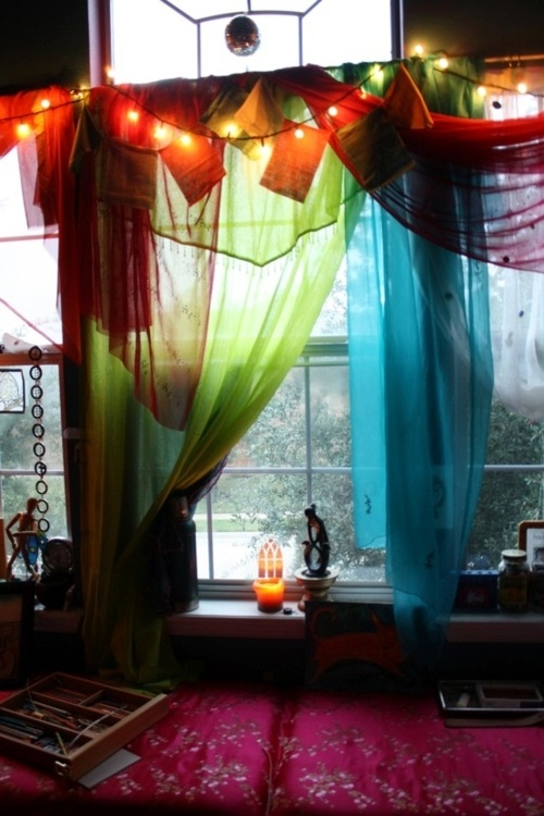 Green and blue sheer curtains with prayer flags and fairy lights