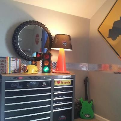 Little boys bedroom. Craftsman tool box dresser that he will own for the rest of his life. We recycled a motorcycle tire and used it for a mirror. Construction cone that I made into a lamp.License plate bookends. Street signs and hub caps on the wall. Hopefully he won't grow out of this room for a long time.