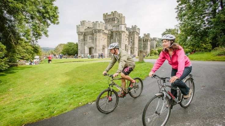 Two people cycle in front of Wray Castle, Cumbria