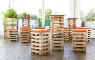 Barkrukken van pallets en hoge tafels van hetzelfde materiaal. Oranje kussens op de zitting.